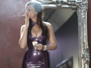 فتاة تدخين السجائر قوية في الأرجواني اللباس اللاتكس